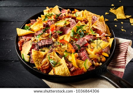 Hot spicy Mexican beef entrecote with nachos, chili peppers and fresh coriander served in an old vintage skillet on a striped kitchen cloth