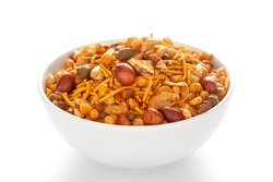 Hot spicy Nav Ratan snacks in a white bowl, made with red chili, peanuts, corn flakes, etc. Pile of Indian spicy snacks (Namkeen), under backlight, side view, against the white background.