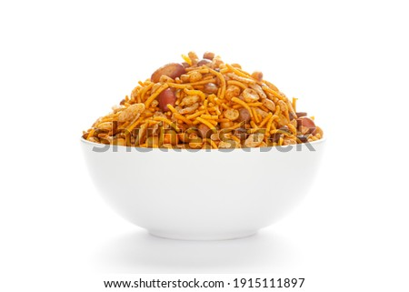 Hot spicy Nav Ratan snacks in a white Ceramic bowl, made with red chili, peanuts, corn flakes, etc. Pile of Indian spicy snacks (Namkeen), under backlight, Front  view, against the white background. Imagine de stoc ©