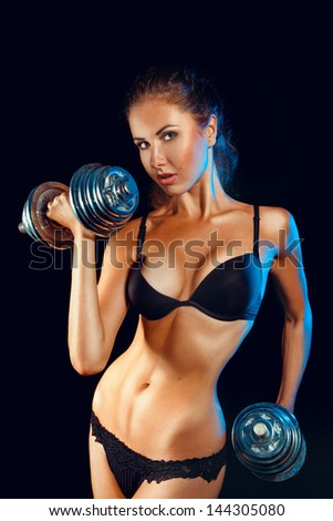 Hot sports girl with dumbbells looking at camera in studio on black background