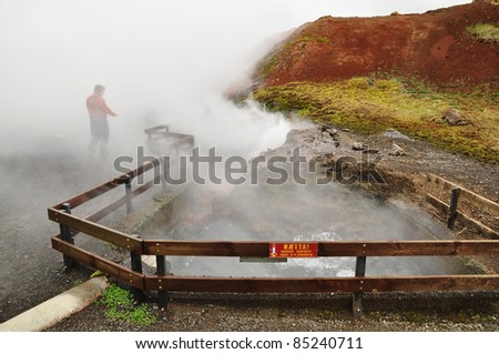 Hot spring and silhouette of standing man, Iceland