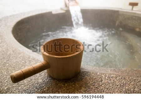 hot spring of stone pool with wooden ladle
