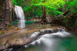 Hot Springs Onsen Natural Bath ,Waterfalls and fish swim in the emerald blue water in Erawan National Park. Erawan Waterfall is a beautiful natural rock waterfall in Kanchanaburi,Thailand.