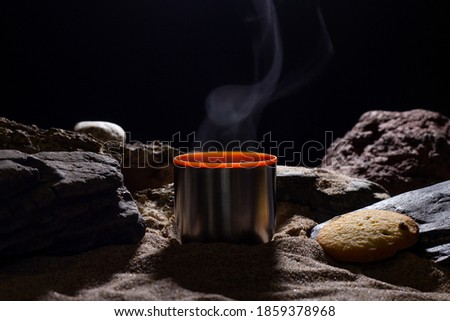 Hot steaming coffee in a stainless steel thermos mug and chocolate chip cookie on a stone and sandy bottom on a cold dark night with a ray of moonlight. Desert and beach background.
