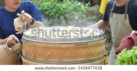 Hot steaming pot with steamed pork dumpling and steam on roadside, chinese traditional menu, foodstuff on street food restaurant #1458477638