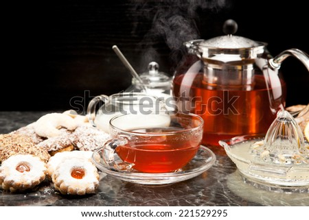 Hot steaming tea with Christmas biscuits