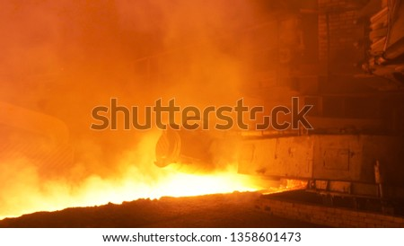 Hot steel production at the steel plant, metallurgy concept. Stock footage. Hot shop with flowing molten steel in the chute. #1358601473