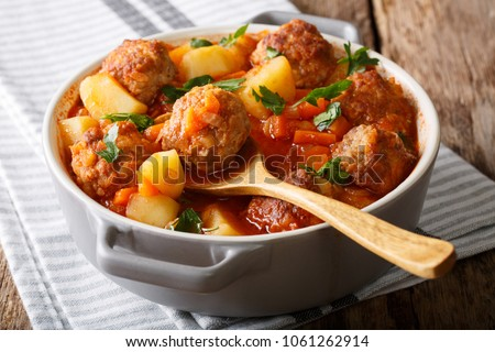 Hot stew meatball soup with vegetables in tomato sauce closeup in a pot on the table. horizontal Foto stock ©