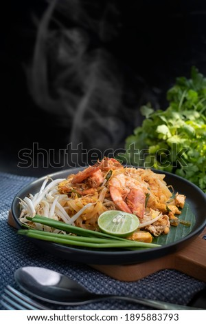 Hot stir fried Pad Thai with shrimp in Thai restaurant. Shrimp Pad Thai or Padthai fried noodles is famous street food of Thailand. Steamy Padthai with shrimp and Thailand street food concept.