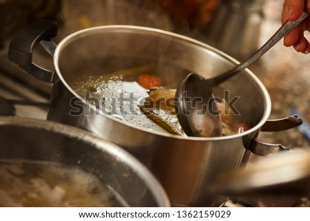 Hot stock pot is stirred by a ladle while it is simmering