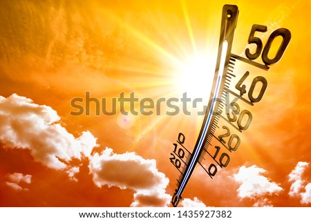Hot summer or heat wave background, glowing sun on orange sky with thermometer