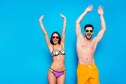 Hot summer time concept. Portrait of cheerful couple in sunglasses and bright swimsuits enjoying sunlight together with beach party mood raise their hands up isolated on bright blue background
