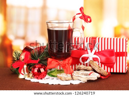 Hot tasty drink with christmas candy and other decorations on bright background