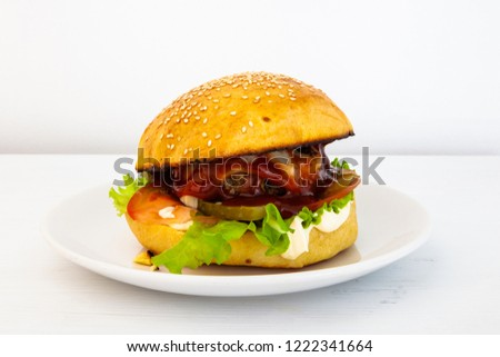 Hot tasty hamburger on a plate on a white background. Homemade hamburger stuffed with beef patties, tomato, pickled cucumber and onion, mayonnaise, ketchup, cheese and salad. Fast food