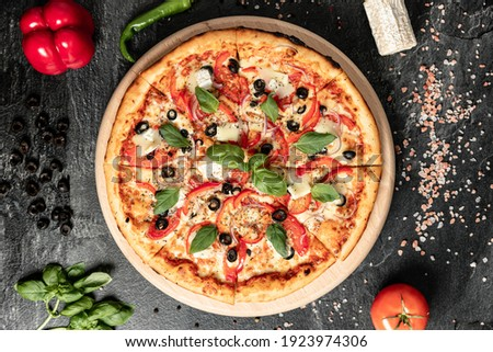 Hot tasty traditional italian pizza with salami, meat, cheese, tomatoes greens on a dark background
