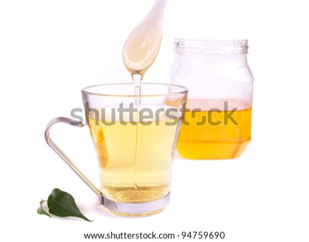 Hot tea and honey pouring from spoon, with jar of honey in the background, isolated on white