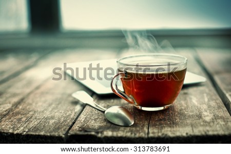 Hot tea cup on a frosty winter day window background #313783691