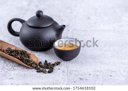 Hot tea in black teapot and cups and dry tea leaves over bright gray cement background, close up, copy space design concept. Foto stock ©