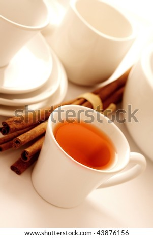 hot tea in cup with cinnamon sticks - stock photo