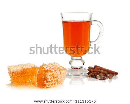 Hot tea in glass cup with spice and honey on white background