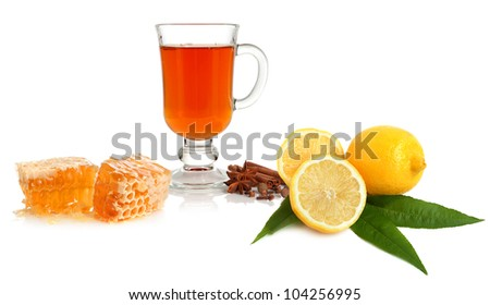 Hot tea in glass cup with spice, lemon and honey on white background