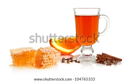 Hot tea in glass cup with spice, orange and honey on white background