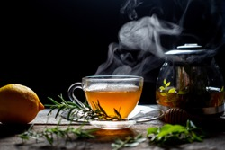 Hot tea in glass cup with steam and lemon .tea leaves and mint herb on wood background