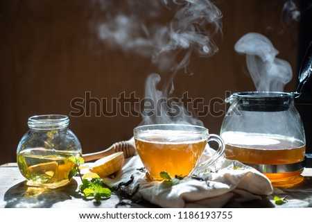 Hot tea in glass teapot and cup with steam on wood background Foto stock ©