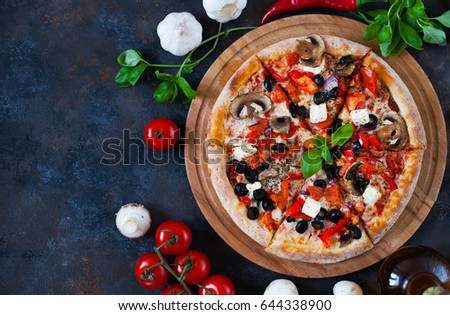 Hot testy pizza with tomatoes, mozzarella, mushrooms, olives, red pepper and basil on black concrete background. Copyspace. Top view. Banner.