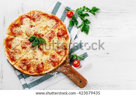 Hot true PEPPERONI ITALIAN PIZZA with salami and cheese. TOP VIEW Tasty traditional pepperoni pizza on board on white wooden table with decoration. Copy space for your logo. Ideal for commercial