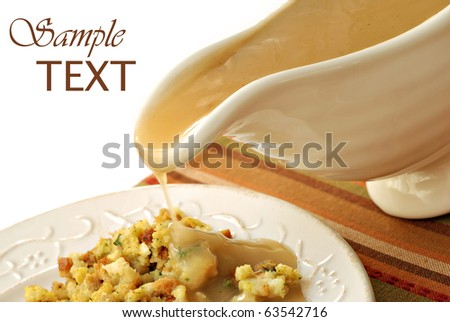 Hot turkey gravy being poured over plate of stuffing on white background with copy space. Slight motion blur on drip.