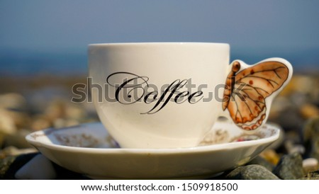 Hot Turkish coffee on the pebble beach. Relaxation mood, resting vacation. Leisure in sunny summer day. Coffee word written on glass. Beautiful view of life with pleasure. Blurred background.