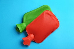 Hot water bottles on light blue background, flat lay
