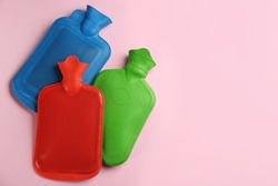 Hot water bottles on pink background, flat lay. Space for text