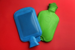 Hot water bottles on red background, flat lay