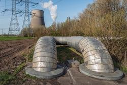 Hot water pipes from a Dutch combined heat and power plant. In the background, a concrete cooling tower, smoking chimneys and electricity pylons and lines are visible against a blue sky.