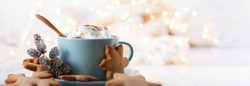 Hot winter drink: chocolate with whipped cream in blue mug. Christmas time. Cozy home atmosphere, white background. Homemade gingerbread cookies, christmas lights. Banner, copy space for text