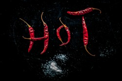 HOT written on a black surface with the help of some red hot chilies. Top shot of red hot chilies making hot word.