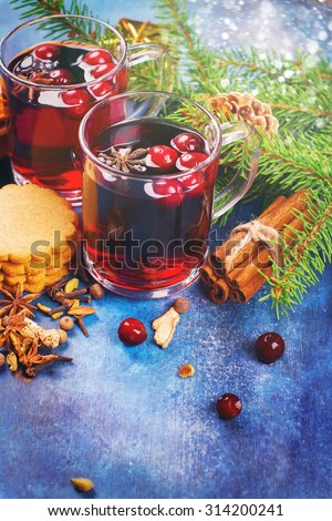 Hot xmas punch with spices and cranberry in glass cups. Xmas or new year concept. Xmas decorations, wooden background. Selective focus. Toned image