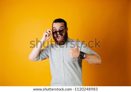 Hot young bearded cheerful man holding sunglasses, laughing at the camera and showing thumb up. Hot offer, summer days.