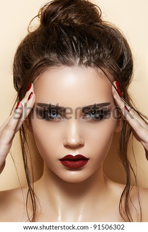 Hot young woman model with sexy dark red lips makeup, strong eyebrows, clean shiny skin and wet bun hairstyle. Beautiful fashion portrait of glamour female face - stock photo