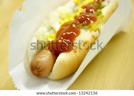 Hotdog fastfood sausage in bun with condiments