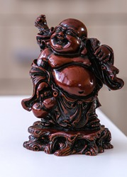Hotei - chinese god of wealth, prosperity and happiness seating in the rocking-chair. Ancient figurine