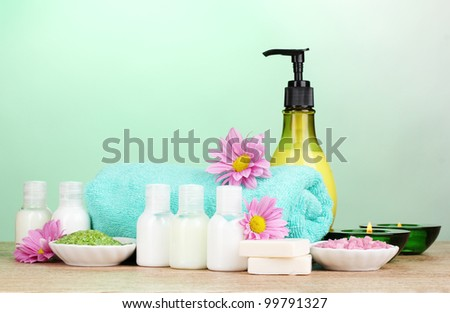 Hotel amenities kit on wooden table on blue background
