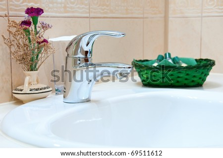 Hotel bathroom: sink, tap and bathroom set