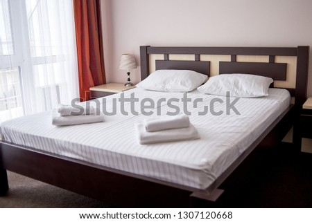 Hotel bedroom interior with empty double bed with wooden headboard, bedside table and big window, copy space. White sheet, soft pillows and towels on bed #1307120668