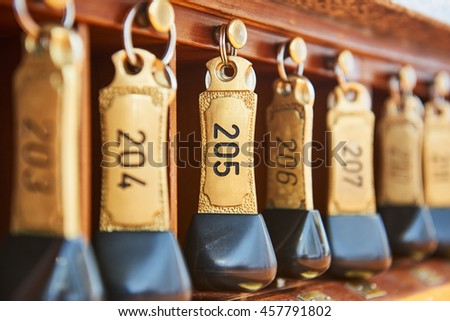 hotel bronze keys with room numbers hanging at reception desk counter