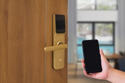 Hotel door security Unlocking by application on mobile phone. Digital door lock, keyless system of access door. Close up and selective focus.
