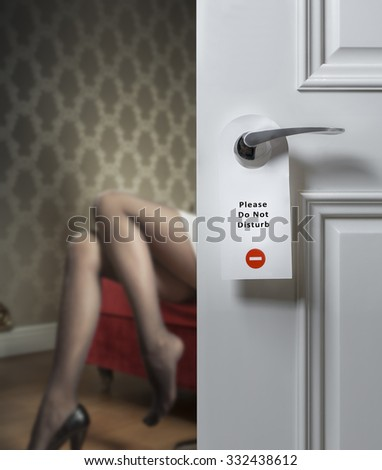 Hotel door with do not disturb icon and sexy female legs on the background; adultery concept
