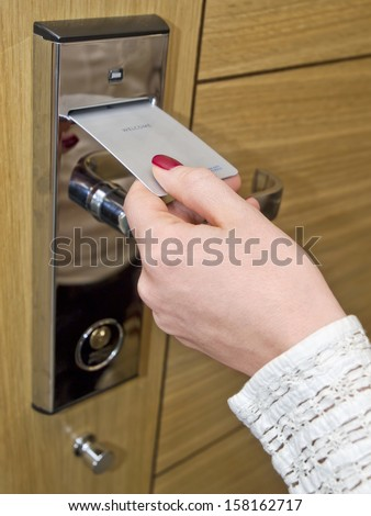 Hotel door - woman's hand inserting key card in an electronic lock